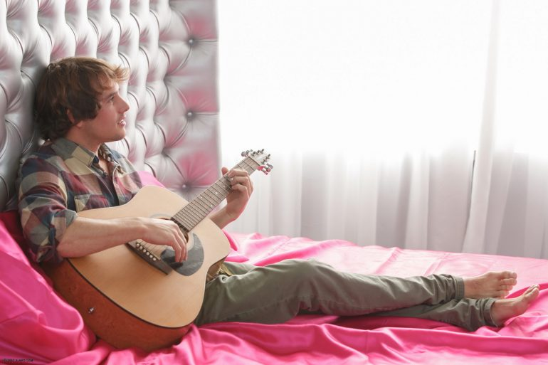 Романтик с гитарой лежит на кровати